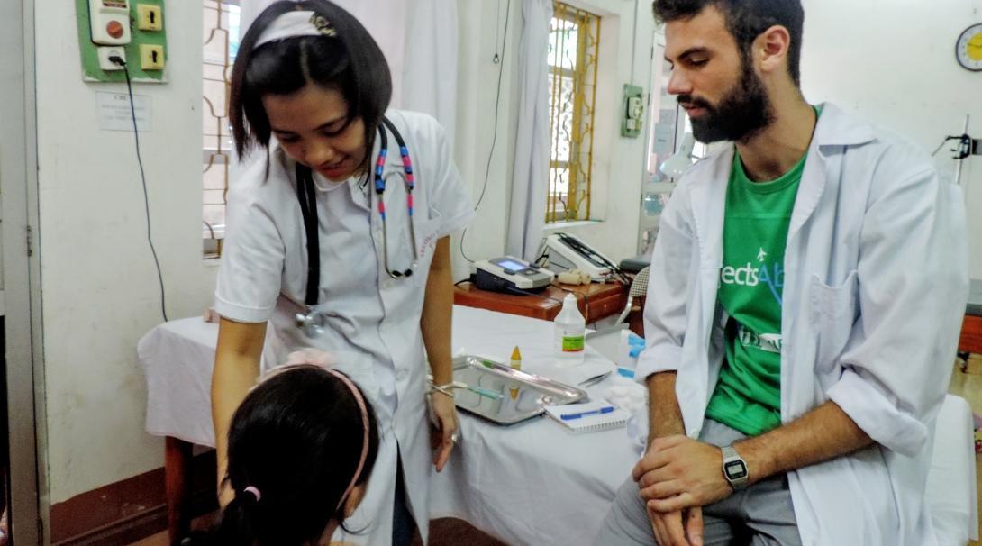 Un interno médico asistiendo a una doctora local durante un examen médico en Vietnam.